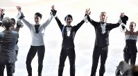 Yuzuru Hanyu, center, greets spectators while holding hands with Evgeni Plushenko, right, and Johnny Weir at the end of the