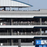 来日するトランプ米大統領の専用機と車列を一目見ようと、羽田空港の駐車場に集まった人たち=羽田空港で2019年5月25日午後4時32分、丸山博撮影