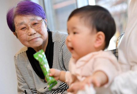 Kimie Kishi looks at her granddaughter in Miyoshi, Hiroshima Prefecture. (Mainichi/Naohiro Yamada)