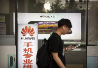 A man looks at his smartphone as he walks past an electronic shop advertising phones from Huawei and Apple in Beijing, on May 24, 2019. (AP Photo/Mark Schiefelbein)