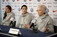 United States women's national soccer team members, from left, Carli Lloyd and Alex Morgan listen as teammate Megan Rapinoe speak to reporters during a news conference in New York, on May 24, 2019. (AP Photo/Seth Wenig)