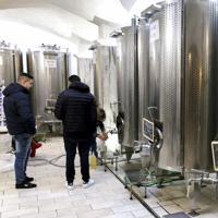 イタリアのワイナリーでは量り売りのワインを求める客が絶えない。多くのワイナリーはブドウの搾りかすを別の蒸留所に委託してグラッパを造る=ローマ近郊ネットゥーノで