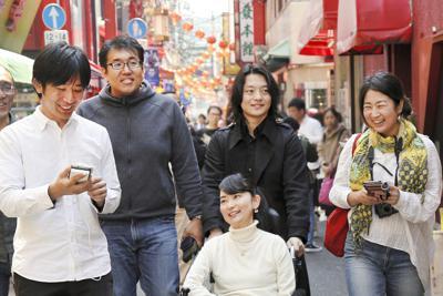夫の洋一さん(左端)らと中華街を散策する織田友理子さん(中央手前)=横浜市中区で、丸山博撮影