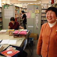 岩田さん(右)はボランティアスタッフと点訳絵本を届けている=大阪市のNPO法人「てんやく絵本ふれあい文庫」で