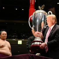 優勝した朝乃山(左)に渡すため、米大統領杯を抱えるトランプ米大統領=東京・両国国技館で2019年5月26日、小川昌宏撮影