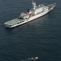 犬吠埼沖で貨物船が衝突した現場付近で、捜索を続ける海上保安庁の巡視船と小型ボート=千葉県銚子市で2019年5月26日午後3時11分、本社ヘリから