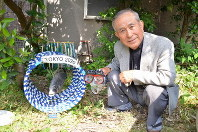 Naoyuki Aoki is seen next to a recreation of the blackhead sea bream swimming through the Tokyo 2020 hoops, in his garden in Matsuyama, Ehime Prefecture, on May 16 2019. The extra rings he prepared for the 20-loop challenge can be seen in the background. (Mainichi/Ryoko Kijima)