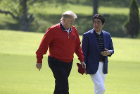 President Donald Trump walks with Japanese Prime Minister Shinzo Abe before playing a round of golf at Mobara Country Club, Sunday, May 26, 2019, in Chiba, Japan. (AP Photo/Evan Vucci)