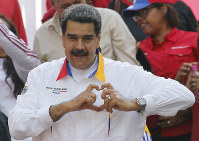 In this May 20, 2109 photo, Venezuela's President Nicolas Maduro flashes a hand-heart symbol to supporters outside Miraflores presidential palace in Caracas, Venezuela.