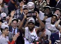 Toronto Raptors forward Kawhi Leonard (2) holds up the trophy after his team's 100-94 win over the Milwaukee Bucks in Game 6 of the NBA basketball playoffs Eastern Conference finals Saturday, May 25, 2019, in Toronto. The Raptors advanced to the NBA Finals. (Frank Gunn/The Canadian Press via AP)
