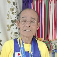 ボストンマラソンの完走メダルを首にかけ、山田敬蔵さんから贈られたメダルを手にする下條道晴さん=東京都八王子市館町で