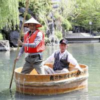 宮川靖司さん(右)の指導を受けながらたらい舟を漕ぐ記者=岐阜県大垣市船町の水門川で