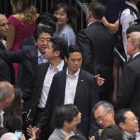 退席するトランプ米大統領(右)を観客席の方へ呼び寄せる安倍晋三首相(中央左)=東京・両国国技館で2019年5月26日午後5時45分、手塚耕一郎撮影
