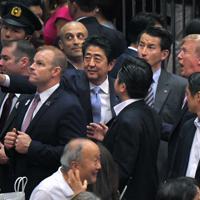 退席時に観客席の方を指し示し、トランプ米大統領(右)を呼び寄せる安倍晋三首相(中央)=東京・両国国技館で2019年5月26日午後5時45分、手塚耕一郎撮影