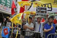 Pro-Beijing supporters destroy yellow umbrellas, used to mark protesting denouncing far-reaching Beijing control, during a demonstration in Hong Kong, on May 26, 2019. (AP Photo/Kin Cheung)