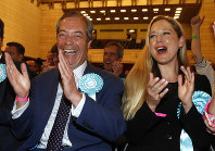 Brexit Party leader Nigel Farage, left, reacts as results are announced at the counting center for the European Elections for the South East England region, in Southampton, England, on May 26, 2019. (AP Photo/Alastair Grant)