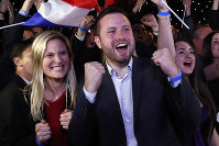 Far-right supporters react at their campaign headquarters in Paris, on May 26, 2019. French polling agency estimates show far-right National Rally expected to beat Macron's party in European elections. (AP Photo/Thibault Camus)