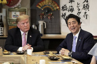 Japan Prime Minister Shinzo Abe, right, speaks during dinner with U.S. President Donald Trump at the Inakaya restaurant in the Roppongi district of Tokyo, on May 26, 2019. (Kiyoshi Ota/Pool Photo via AP)
