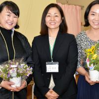歓迎の花束を手にするボリバヤル・オトゴントヤさん(左)とバトヒシグ・ウヤンガさん(右)。中央は片桐真奈美理事長=茨城県守谷市野木崎で