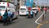 Victims of a May 28, 2019 stabbing attack are taken to waiting ambulances in Tama Ward, Kawasaki, Kanagawa Prefecture. (Mainichi/Makoto Shinno)