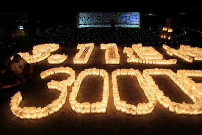 東日本大震災から3000日となり「がんばろう石巻」と書かれた看板の前で灯された追悼のキャンドル=石巻市で2019年5月28日午後7時48分、和田大典撮影