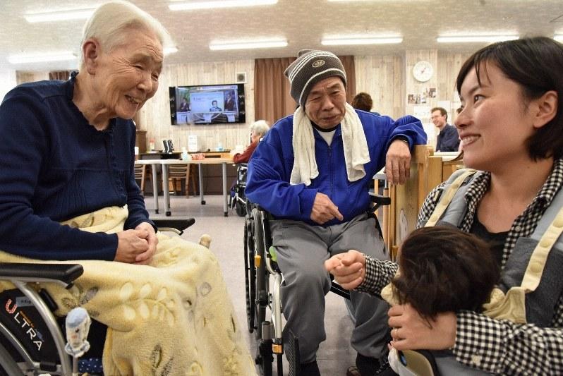 田端香さん(右)と長女の芽彩ちゃんの姿をみて笑顔をみせる入居者=神戸市で、筆者撮影