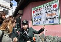 A staff member for the Kyoto city transportation bureau guides passengers to separate sightseeing and local routes at a bus stop near Kinkaku-ji Temple in Kyoto's Kita Ward on April 27, 2019. (Mainichi/Ai Kawahira)