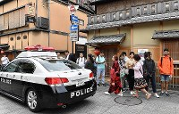 A police car on patrol broadcasts announcements that the street is not pedestrian-only in several languages in the Gion district of Kyoto's Higashiyama Ward on May 14, 2019. (Mainichi/Ai Kawahira)