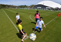 J-Village, Fukushima Prefecture -- This file photo taken on April 20, 2019 shows children playing a match at the national soccer training facility, now fully reopened after its closure due to the 2011 Great East Japan Earthquake and the ensuing Fukushima Daiichi Nuclear Power Station disaster, in the prefectural town of Naraha in northeastern Japan. (Mainichi/Toshiki Miyama)