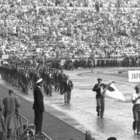 開会式でプラカードと日の丸を先頭にメインスタンド前を入場行進する日本選手団(国名はフィンランド語表記)=フィンランド・ヘルシンキ・オリンピックスタジアムで1952年(昭和27年)、安保久武特派員撮影