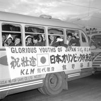 バスの中から日の丸の小旗や手を振る選手たち。岸記念体育会館から羽田空港に向かう一行のバスに、沿道の人々は激励の声をかけた=1952年(昭和27年)6月28日