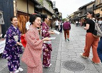 Maiko dancers are seen in the Gion district of Higashiyama Ward, Kyoto, encouraging visitors to mind their manners, on May 14, 2019. (Mainichi/Ai Kawahira)