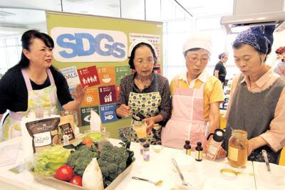 ローカレーに使う香辛料について説明する山口和美さん(左端)。調理台には地場産の新鮮な野菜が並ぶ=神奈川県厚木市で5月24日
