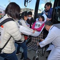 富士吉田市立病院で実施された入院患者の避難を想定した訓練で避難用に貸し切った大型バスに運び込まれる患者役。成人男性数人がかりでも狭い車内では手こずる様子も見られた=山梨県富士吉田市で2018年11月25日、宮間俊樹撮影