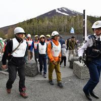 富士山の噴火を想定した避難訓練をする参加者ら。避難誘導係をした参加者は「その場で各自が考えて行動したところも多かったが、事前に自分たちの行動について避難経路などの情報共有が重要だと改めて思った」=山梨県側の富士山5合目で2019年5月31日、宮間俊樹撮影