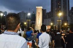 追悼集会の会場で、犠牲者の慰霊碑を見つめる中国人男性(左手前)=香港中心部のビクトリア公園で2019年6月4日午後7時14分、福岡静哉撮影