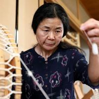 糸車で糸を紡ぐ浜田スミ子さん=東大阪市で、幾島健太郎撮影