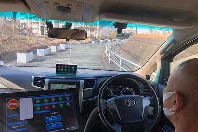 多摩ニュータウンの団地内を走る自動運転車。緊急時に備えて乗務員がハンドルに手を添える=東京都多摩市内で2月23日