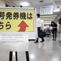 システムで処理する業務ができず、来訪者に頭を下げる市職員=大阪市中央区役所で2019年6月7日午後5時48分、小出洋平撮影