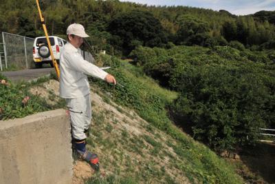 大雨に削られる被害を受けた土手を指さす朝倉さん