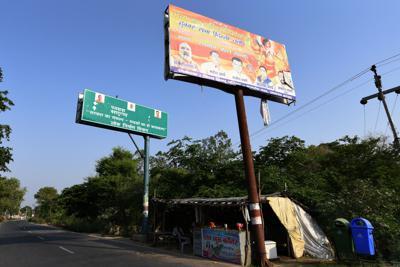 手前の看板は、ヒンズー教のラーマ神の生誕地への寺院建設を求めるRSS関連団体による集会の告知。後ろの標識は政府が道を作り変えたことを知らせるもので、モディ首相らBJPの政治家の顔写真が張られていた=インド北部ウッタルプラデシュ州で2019年6月、松井聡撮影