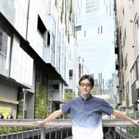 渋谷川の橋の上に立つ小宮山雄飛さん。左は「渋谷ストリーム」=東京都渋谷区で、内藤絵美撮影