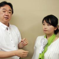 「えりかけ扇風機」の使い方を説明する豊田哲郎さん(左)=さいたま市中央区で