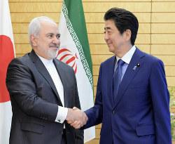 イランのザリフ外相(左)と各種する安倍首相。米イランの「仲介役」の成果は……(首相官邸で5月16日)