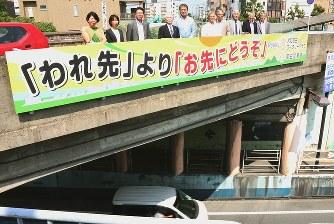 県道5号にかかる交通標語看板を交換した大和高田ロータリークラブのメンバーら=大和高田市高砂町で