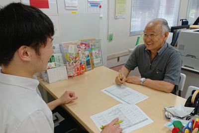 仕事の打ち合わせをする山本さん(右)。「異なる世代の人と交流できて刺激になる」と話す=東京都大田区で