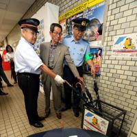大阪メトロ都島駅に設置された、特殊詐欺被害防止イラストを描いた傘=大阪市都島区で2019年6月13日、幾島健太郎撮影