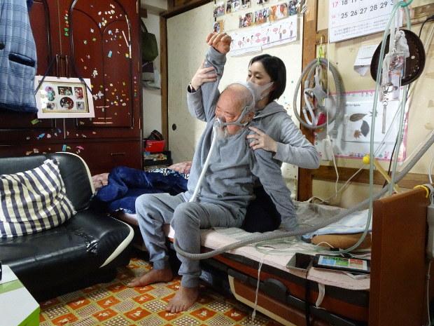 石山さん(奧)によるリハビリを受ける田島さん。リハビリの際は人工呼吸器を装着する=川崎市内で2019年3月20日、鈴木敬子撮影