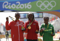 In this Aug. 14, 2016 file photo, silver medalist Eunice Jepkirui Kirwa, of Bahrain, left, gold medalist Jemima Jelagat Sumgong, of Kenya, center, and bronze medalist Mare Dibaba, of Ethiopia stand on the podium after the women's marathon at the 2016 Summer Olympics in Rio de Janeiro, Brazil. (AP Photo/Robert F. Bukaty)