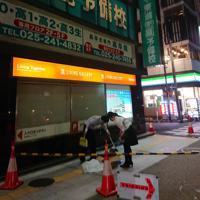 割れて落下したビルの窓ガラスを片付ける人=新潟市中央区で2019年6月18日午後11時31分、井口彩撮影